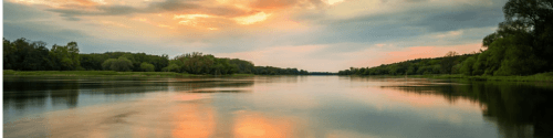 tafereel met water en op de achtergrond bos en rode luchten die in het water reflecteren