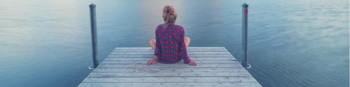 je ziet een vrouw zitten vanaf haar achterkant, ze zit aan de waterrand op een vlonder, ze zit voor zich uit te staren en te genieten van de rust