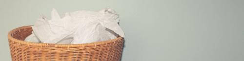 een rieten prullenmand die vol zit met papieren zakdoekken, de emmer is vol en loopt over