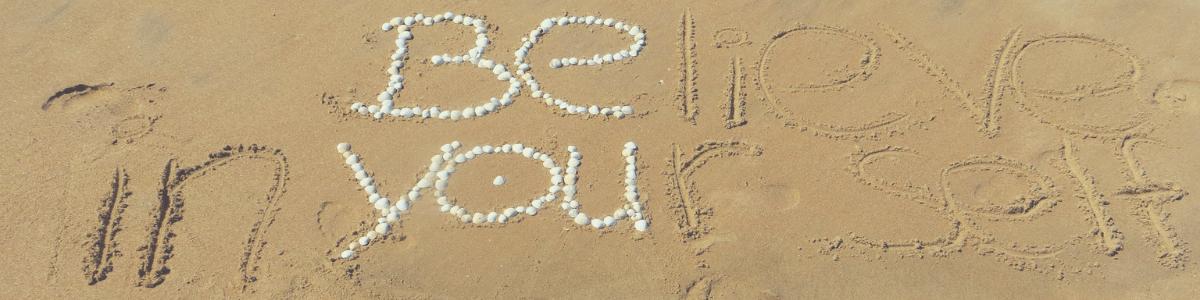 in het stand staat met kiezels geschreven BE YOU, met de hand is in het zand een aanvulling geschreven belief in your self
