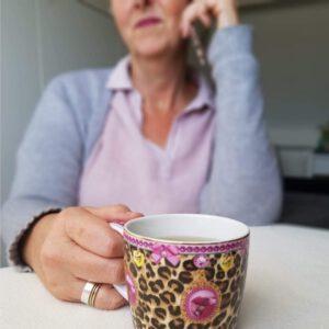 Zuiver Bewust, Saskia op de achtergrond aan de telefoon met een kop heerlijke thee op de voorgrond